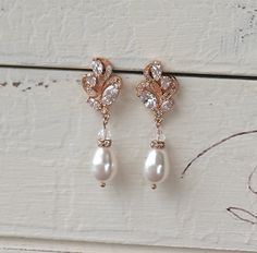 Rose Gold Bridal earrings made with Swarovski crystals are set in a graceful leaf shaped design for a classic and delicate earring. A Swarovski pearl teardrop in your color choice creates the perfect accessory for your wedding. We have used ivory white pearls in the photos. Choose your colors from the drop menu.  These earrings have such a lovely sparkle and would make a beautiful Bridesmaids accessory.  💜 Available in rose gold, silver (rhodium) and gold Measurements: Length - 1.25 Width…