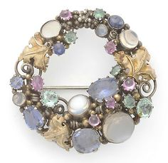 Dorrie Nossiter. Arts and Crafts brooch. The hoop frame of gold leaves, silver scrolls and beading is set with cabochon moonstones, assorted sapphires and pink and green tourmalines in a mixture of claw and collet settings, measures 4.8cm in diameter. Sold by Tennants. View 1.