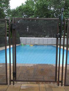 Brown self closing pool fence gate.