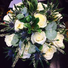 wedding flowers Blue thistle heather and ivory roses in a brides hand tied bouquet