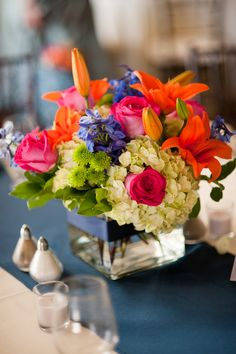 bright colors for table arrrangements (replace roses with other pinkish flower) - Clear cube with lilies, roses, hydrangea, delphinium & button mums