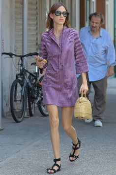 Alexa Chung wearing pajama inspired pin striped henley dress with black strappy sandals, oversized black oval sunglasses, and wicker basket style handbag.