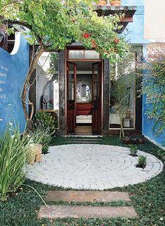 O piso intervalado disposto em círculos deu movimento à entrada da casa. Algumas pedras foram dispensadas para que ali se cultivassem pequenas plantinhas. Projeto de Paula Galbi.