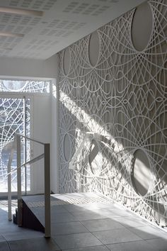 This lobby in this building features decorative concrete panels inspired by a pattern found on bank notes. The artistic panels also cover the facade of the building.