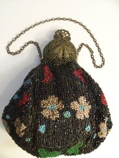 Antique beaded purse w delicate, lush, filigreed antique beaded purse.  I love the faceted iridescent beads that are the background for the bright flowers on this purse.  It is so heavily pleated that it is hard to photograph the details.