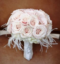 Pink bouquet with white feather accents and bouquet jewelry on the stems