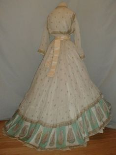 A stunning 1860's Civil War era paisley print cotton two piece dress.  The fabric has a small paisley pattern and a large aqua paisley print around the edge of the hemline. The bodice has pagoda styled sleeves that are trimmed with paisley print and the inside of the cuff is trimmed with lace.  The neckline is also trimmed with lace.  The shoulders, armscyes and lower waist are all piped.  The bodice is unlined.  There are no hook and eye closures and does not appear to have ever had them…