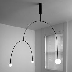 Arrangements of illuminated globes balanced on delicate metal supports form lamps in London designer Michael Anastassiades' updated range