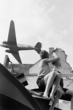 German children watching the flight low-flying American transport aircraft C-47 'Skytrain' (Douglas C-47 'Skytrain') over the destroyed home in Berlin, 1946.    Histomil.com