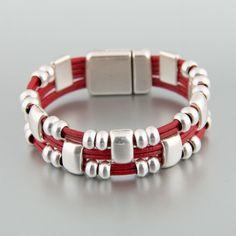 Pulsera elaborada en cuero redondo rojo con adornos en zamak bañado en plata y cierre de imán rectangular en zamak bañado en plata
