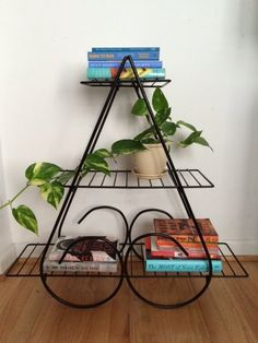 Unique 3-tiered plant stand made from black metal.