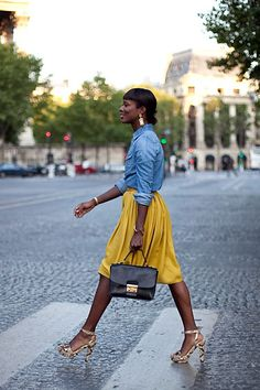 denim shirt worn beautifully with mustard skirt...heels adding an element of sophistication and class to denim