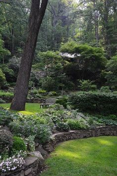 enchanting garden with shade loving plants and low, stacked stone retaining walls.