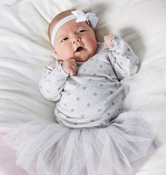 This cheeky cherub is ready to party (well, OK maybe ready to go to bed). Shop this sweet party look now and get 40% off.  Milky Foil Spot Knit Milky Party Skirt Grey & Silver Small Bambini Bow Band in White