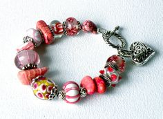 This bracelet was created with handcrafted artisan lampwork glass beads and Rhodochrosite, Pink Turquoise, silver beads,caps and toggle