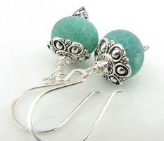 These beautiful earrings are made with emerald green matte fire agate rondelles. Each rondelle is nestled on a Bali silver fancy teardrop headpin and capped with a beautiful silver bead cap. Each rondelle is dangling from a fancy rounded sterling silver earring.     MEASUREMENTS: Earrings dangle ...