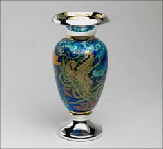 Fred Rich Enamel Design. Silver, silver gilt, and enamel with 22ct gold cloisson. This delightful vase was inspired following a visit to the Great Barrier Reef. The design includes Lemon Angel Fish and a Box Puffer Fish, and this image shows two Seahorses lovingly entwined. The height of the vase is 220mm.