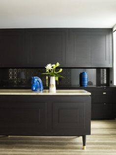 LOVE this trend of the islands that look like sideboards   Black kitchen cabinets - designer: Greg Natale