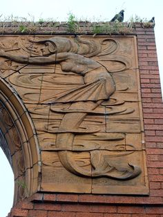 The Mermaids Archway, West Bridge. Formerly spandrels at the entrance to the wholesale market in Halford Street, removed in 1972 and reset by West Bridge in 1980. Designed by William Neatby in 1900 and made by Doulton.