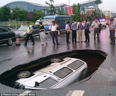 That sure is some pothole: Stunned onlookers stand and gawp at the 6ft deep sinkhole which swallowed up a minibus in Guilin, China, this morning 6/8/12