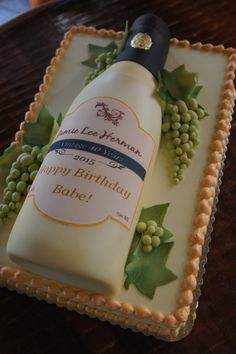 Champagne bottle birthday cake with customized label and grapes on top of sheet cake