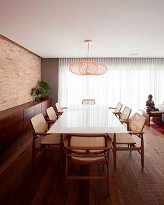 Decoração de apartamento moderno e rústico e ambiente integrados. Na cozinha parede de tijolinhos brancos, mesa de jantar retangular e cadeira de madeira e pendente.