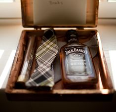 A gift for the groomsmen: cigar, bowtie, and a bottle of Jack.