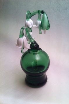 Flameworked in Ithaca New York USA Emerald Green Glass Bottle Estimated Dimensions, 3 inches tall by 2.5 inches wide Holds around 3 fluid ounces White Glass Lily of the Valley with Emerald Green Glass Stem Estimated Dimensions, 4 inches long by 1.5 inches wide Total Estimated Height