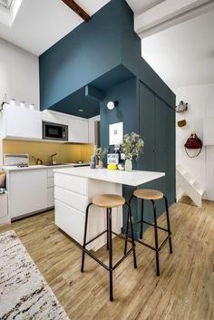 Cuisine blanche et mur bleu Une vue de la mezzanine depuis le coin salon