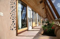 Like the division of room by windows and curtains :) Corner Cottage Earthship greenhouse by Earthship Kirsten, via Flickr