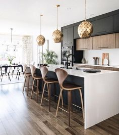 A stylish modern kitchen with a combination of poly, timber and stone. Cool pendants and bar stools.