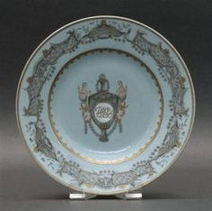 """CHINESE EXPORT PORCELAIN PLATE 18th Century  Central polychrome and gilt decoration of a monogrammed covered urn and floral garland flanked by two mermaids. Grisaille and gilt border. Diameter 9""""."""