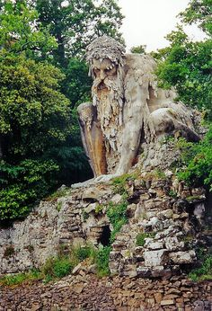 Medici Pratolino Garden ruins in Tuscany, Italy.Shrouded within the park of Villa Demidoff, there sits a gigantic 16th century sculpture known as Colosso dellAppennino, or the Appennine Colossus. The brooding structure was first erected in 1580 by Italian sculptor Giambologna. Like a guardian of the pond in front of him, the giant is in an endless watchful pose, perched atop his earthy seat.