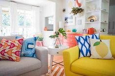 Decorating, Pastel Greenish Yellow Fabric Sofa With Mango Print Pillow And Blue And White Hexagonal Lines Pillow Light Grey Fabric Cushion Sofa With Square Pillows Orange And White Stripes Area Rug Side Table: Mid Century Living Room Design