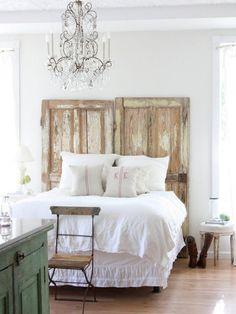 chambre à coucher blanche aménagée avec un mobilier vintage et un lustre de pampilles