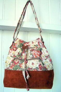 Bolsa Saquinho em tecido 100% algodão dublado ,  com estampa folk.  Fundo em camurça caramelo.    Bolso frontal com zíper.  Forrada e com bolso interno.  Alça regulável    Medidas:  altura: 32 cm  largura: 26 cm  profundidade: 15 cm