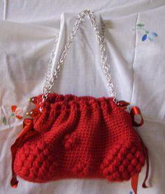 In lana rosso fuoco e manico in catena.