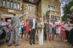 Bride, Groom and guests at their Highgate house wedding venue, throwing confetti.