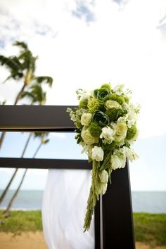 Green and white blooms by Maui Floral enhance the top corners of our arch for Lee & Carl's wedding. Photo: Anna Kim Photography