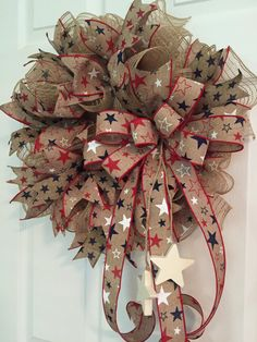 This patriotic Wreath is made of poly jute deco mesh and accented with canvas tan ... red white and blue Stars ribbon. I also used a canvas ribbon that is accented with blue stars. And canvas ribbon accented with red stars. A red white and blue stars now is attached and white wooden stars dangle from the bow. If you want an Proud of our Air Force or Proud of our Navy metal star added to the wooden stars attached to the bow let me know at checkout. This wreath measures approximately 20 ...