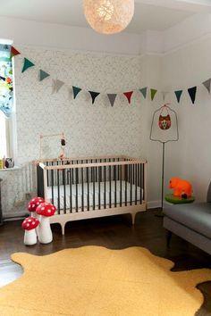 Gender-neutral nursery - black-and-white mushroom wallpaper & bright colors.