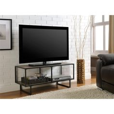 A slim profile gives this fashionable TV stand its sleek, contemporary look. A great addition to virtually any decor, the Emmett TV Stand from Altra Furniture features an industrial chic metal frame in Altra's gunmetal grey finish.