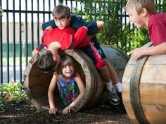 MCPL Nature Explorium Children playing with wooden barrels - outdoor play
