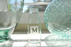 Empty Frappuccino bottles etched with guest initials - too cute!