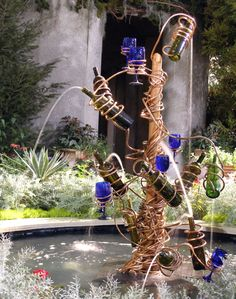 76 Backyard and Garden Waterfall Ideas If you like to entertain, this is the perfect design for your outdoor gathering space. Brightly colored glasses and wine bottles pair up to help set the mood for a fun and lively crew of company. Wine Bottle Fountain, Diy Fountain, Wine Bottle Art, Bottle Garden, Wine Bottle Crafts, Wine Bottles, Fountain House, Glass Garden, Gazebos Ideas