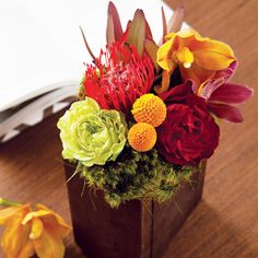 exotic elegance, pincushion protea, cymbidium orchids, safari sunset, craspedia baubles, sunflower pods and ruffled roses