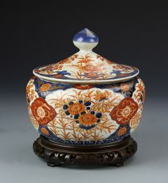 Japan, Imari bowl with colorful floral patterns and carved wooden stand