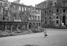 "A German woman strolls past a sign saying ""Hitler's Work"" several weeks after the end of World War II in Europe which had resulted in the destruction of most German cities. 1945."