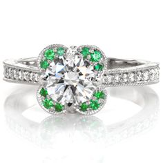 Design 3146 is a Knox Jewelers custom engagement ring created in Minneapolis, Minnesota. This setting features a round brilliant diamond highlighted by a unique shaped crescent halo set with vivid green emeralds. Vintage inspired details like a tapering band and hand engraving add the finishing touches to this colorful ring.