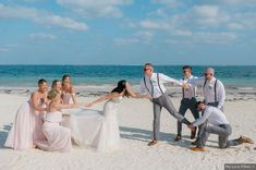 Fun wedding photography of bridesmaids and groomsmen pulling bride and groom apart